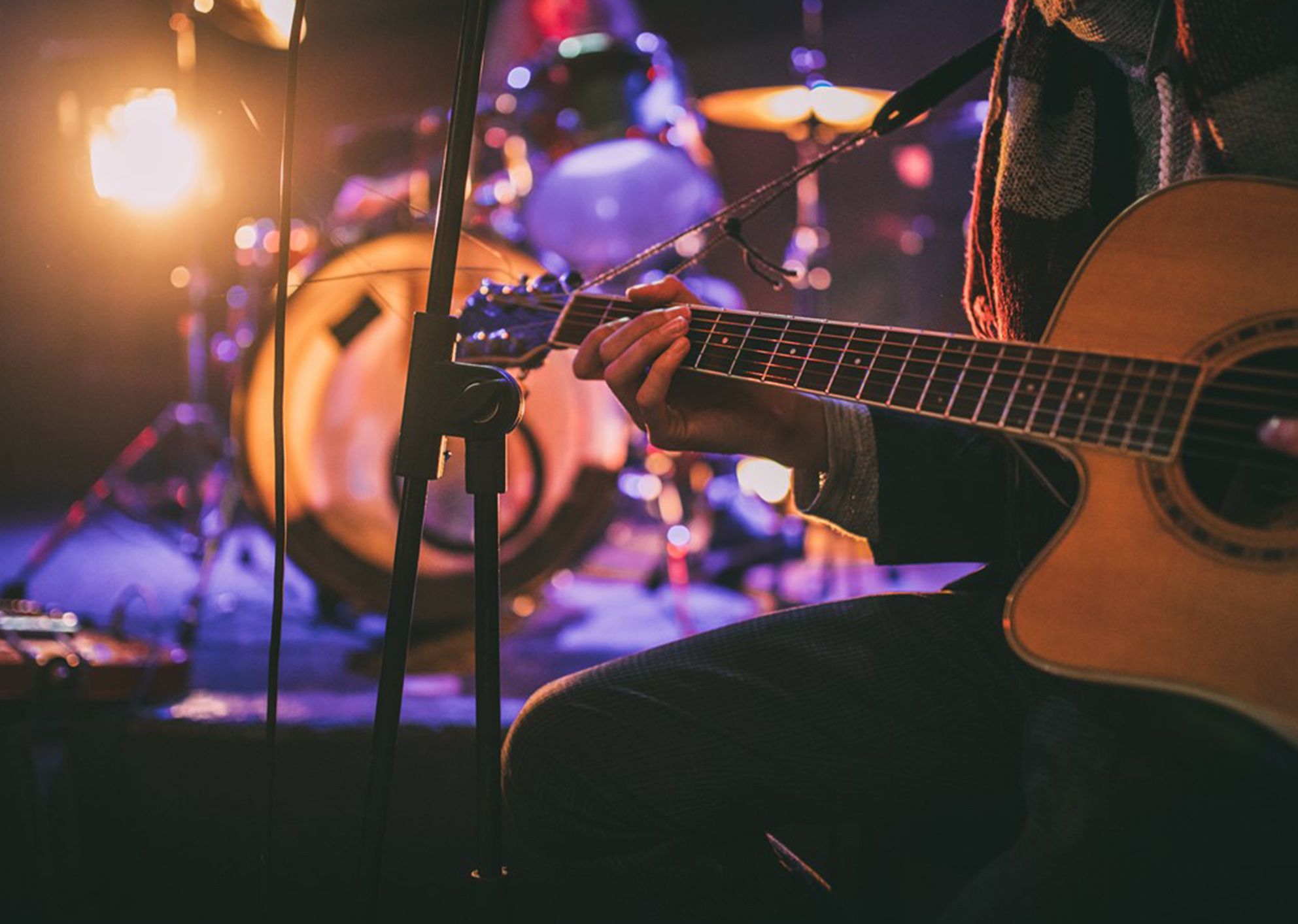 low light, close up of a person playing the guitar. a drum kit is blurred in the background