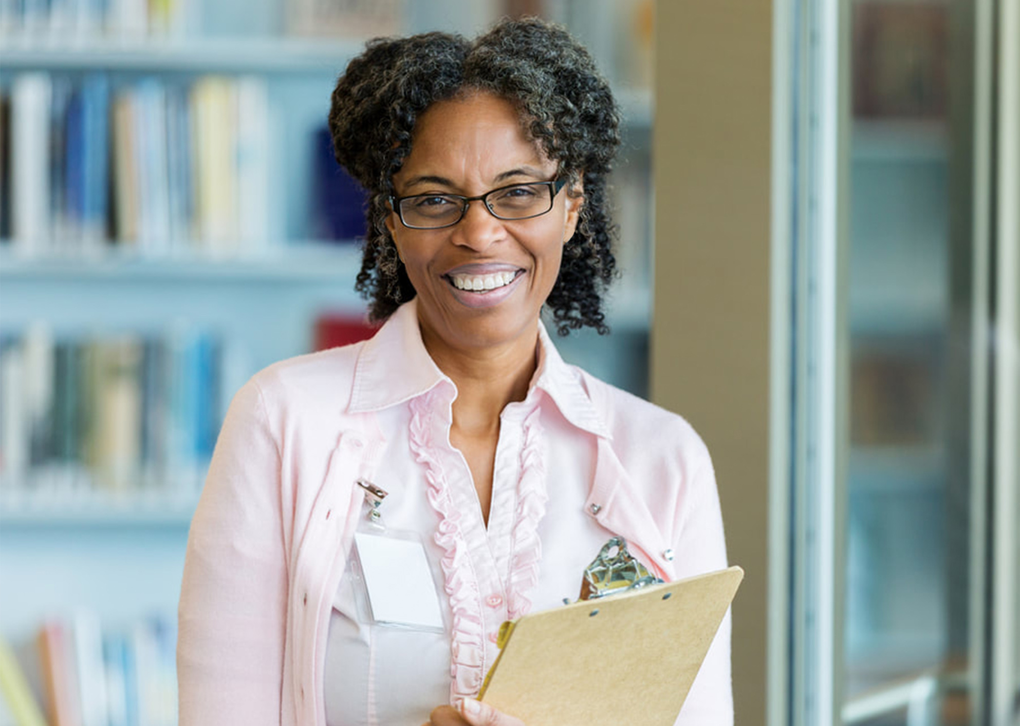 an smiling african american older woman with glasses. she is holding a clipboard in front of bookshelves filled with books. She is wearing a light pink blouse and cardigan with a name tag on her shirt.