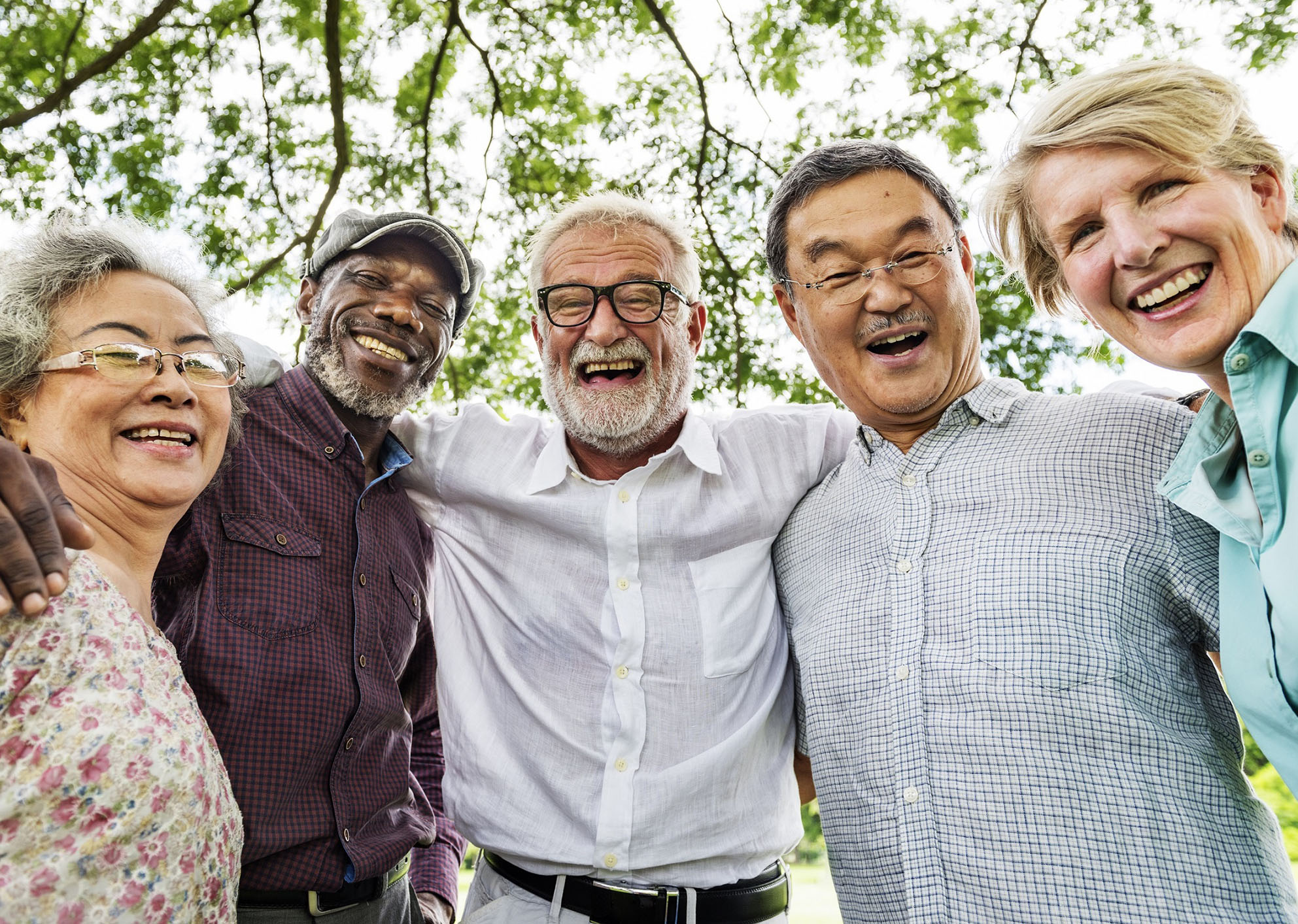 a group of 5 multicultural seniors smiling with trees in the background
