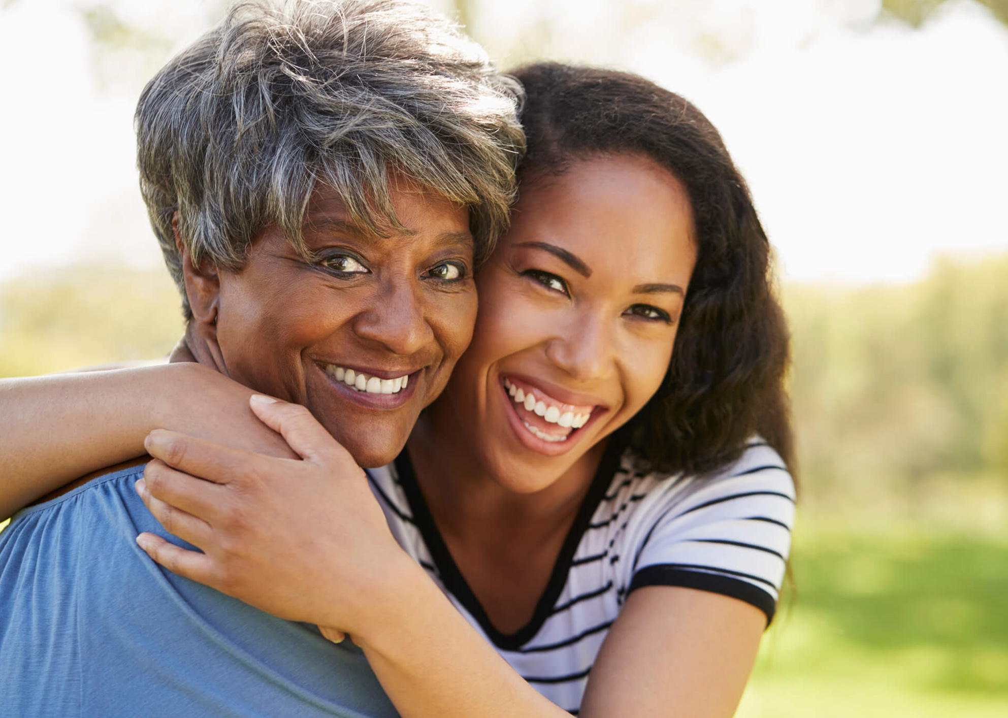 young african american adult hugging and smiling with an older african american lady with grey hair